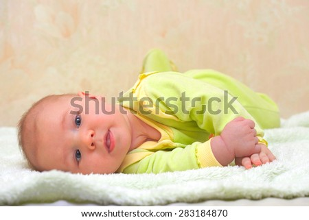 Adorable baby boy lying on a bed - stock photo