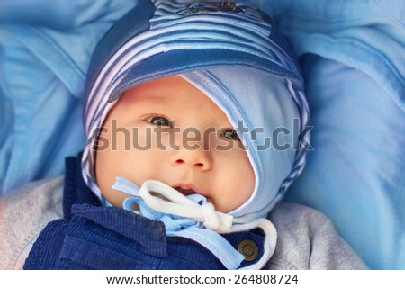 Adorable baby boy on a blue blanket, with a double protection of two blue hats on his head, looking at the camera with a sweet expression - stock photo