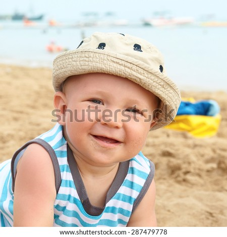 Adorable baby boy on a sand beach - stock photo