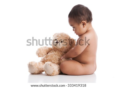 Adorable baby boy playing with a teddy bear.  Isolated on white with room for your text. - stock photo