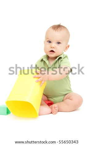 Adorable Baby Boy sitting and playing with blocks and shapes, on white background