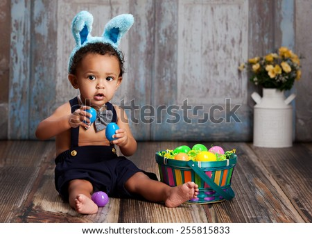 Adorable baby boy sitting on a rustic wood floor, playing with an Easter Basket full of plastic eggs and wearing blue bunny ears.