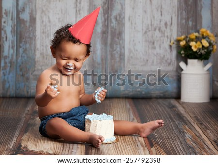 Adorable baby boy, sitting on a wood floor, wearing a party hat and eating a small cake.  Room for your text.