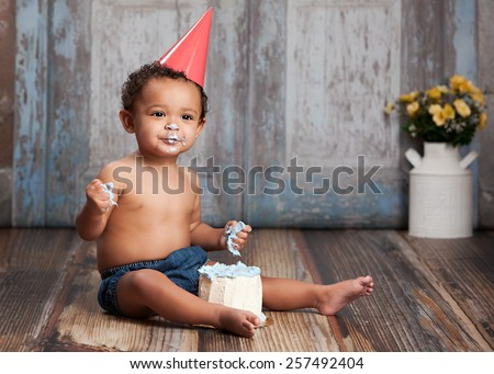 Adorable baby boy, sitting on a wood floor, wearing a party hat and eating a small cake.  Room for your text.  - stock photo