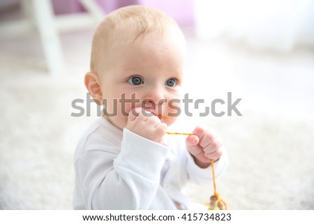 Adorable baby boy sitting on the floor, close up