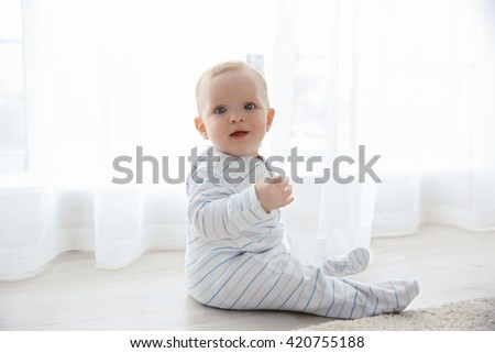 Adorable baby boy sitting on the floor, close up - stock photo