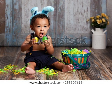 Adorable baby boy sitting on the floor playing with plastic Easter Eggs and wearing bunny ears.