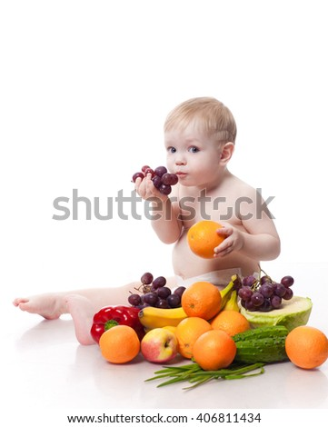 Adorable baby boy sitting with fruits and vegetables