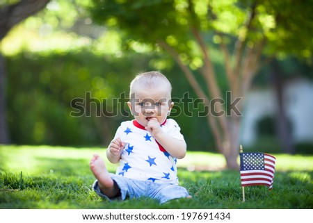 Adorable baby boy siutting on a lawn with American flag