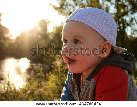 adorable baby boy smiles surprised outdoors. close-up portrait.  - stock photo