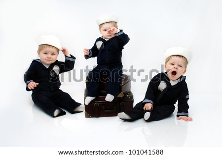 Adorable baby boy wears a navy serviceman costume.  He is yawning and leaning on one hand in an all white room with space for personalization. - stock photo
