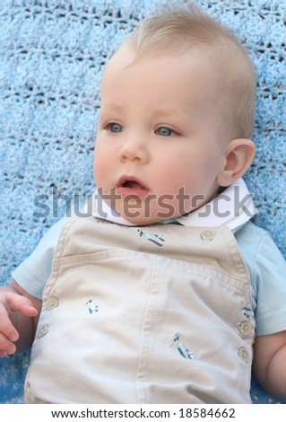 Adorable baby boy with blue eyes on blue blanket / background
