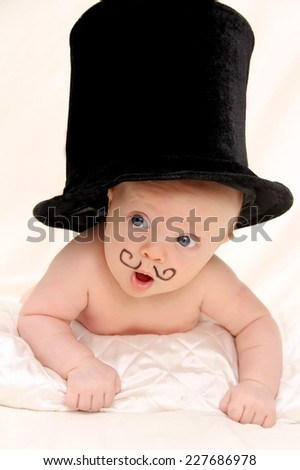 Adorable baby boy with funny mustache and black  top hat - stock photo