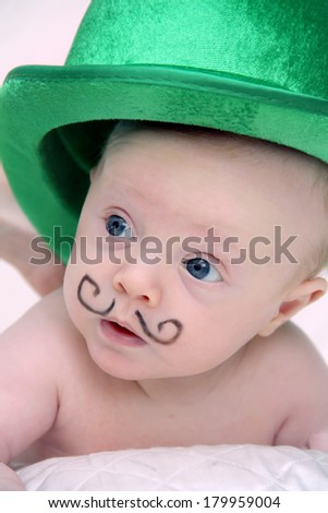 Adorable baby boy with funny mustache and green hat - stock photo