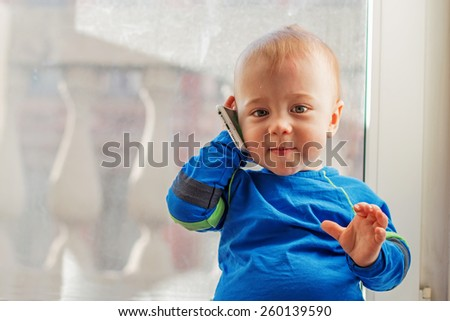 Adorable baby boy with mobile phone - stock photo