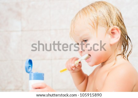 Adorable baby brushing teeth staying in bath