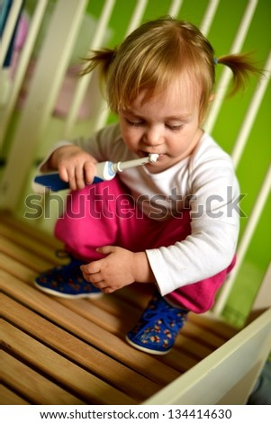 Adorable baby brushing teeth staying in bath - stock photo