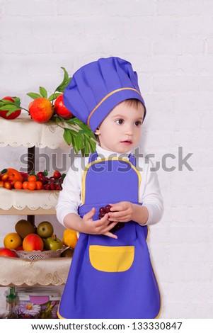 adorable baby cooking in kitchen. little cute child in costume of Cook