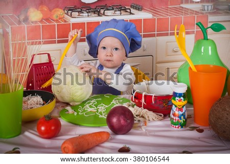 adorable baby cooking in kitchen. little cute child in costume of Cook. funny child makes a dinner. happy cute little baby in a cook cap laughs. Baby cook with vegetables in studio - stock photo