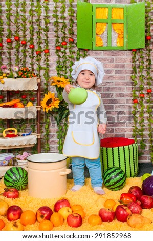 adorable baby cooking in kitchen. little cute child in costume of Cook. Pretty beautiful boy covered in flour makes cakes.baby girl - stock photo