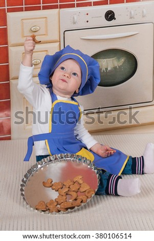 adorable baby cooking in kitchen. little cute child in costume of Cook. Pretty beautiful boy covered in flour makes cakes.Little baby girl is cooking, kneads dough baking, pastry rolls out - stock photo