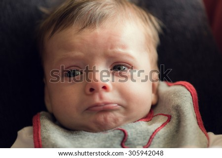 Adorable baby crying and being sad