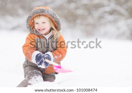 Adorable baby dig with small shovel in snow park - stock photo