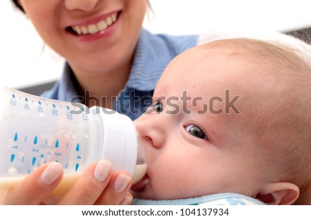 Adorable baby drinking a bottle - focus in the face - stock photo