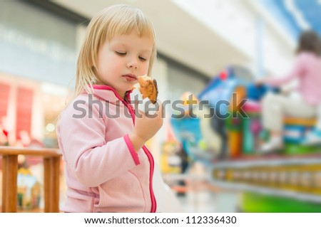 Adorable baby eat donut with chocolate holding it with napkin in mall