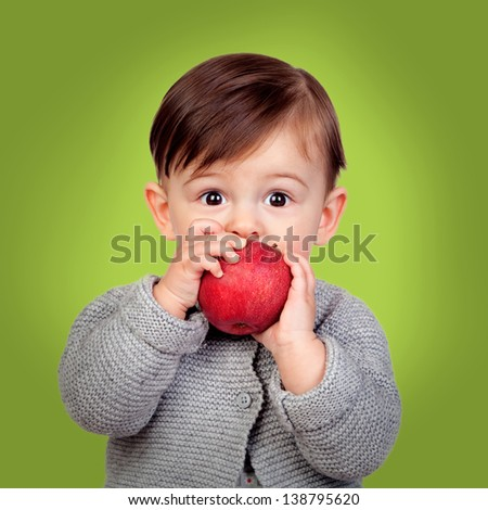 Adorable baby eating a red apple on a green background - stock photo