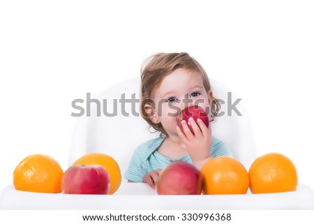Adorable baby eating apple and oranges, healthy food concept - stock photo
