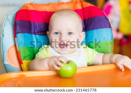 Adorable baby eating in high chair. Baby's first solid food - stock photo