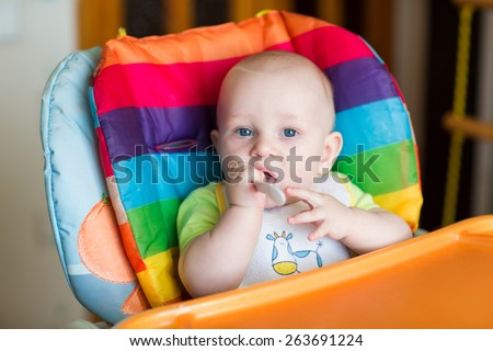 Adorable baby eating in high chair. Baby's first solid food