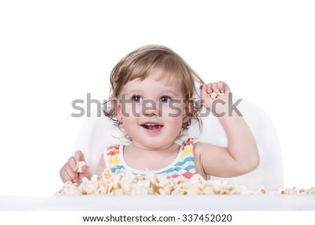 Adorable baby eating popcorn - stock photo