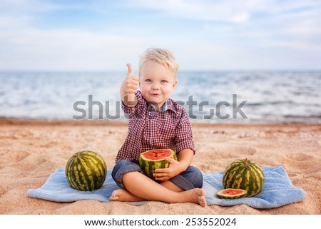 adorable baby eating watermelon on the beach - stock photo