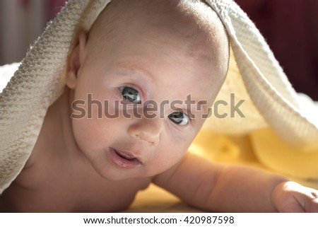 Adorable baby girl covered in a shower towel - stock photo