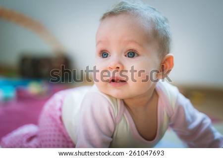 Adorable baby girl crawls on all fours on floor at home. Smiling infant of 6 months playing on ground and looking at camera. Portrait of female child. Vertical, front view. Funny kid goes forward