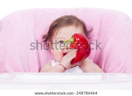 Adorable baby girl eating red pepper - stock photo