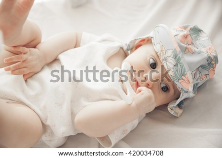 adorable baby girl holding a hand in the mouth isolated on white background - stock photo