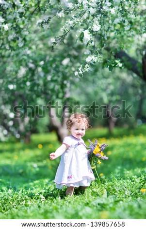 Adorable baby girl in a beautiful apple tree garden - stock photo