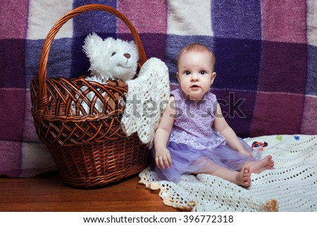 Adorable baby girl in a lilac dress sitting near wicker basket - stock photo