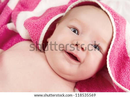 Adorable baby girl in pink blanket smiling