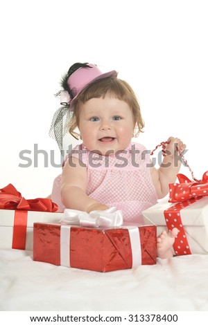 Adorable baby girl in pink clothes with gifts  on a white background - stock photo