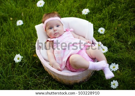 Adorable baby girl in the basket - stock photo