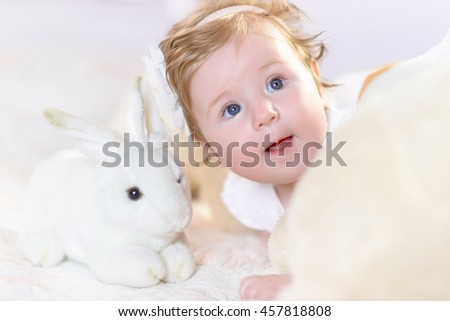 Adorable baby girl in white and pink sunny bedroom. Newborn child relaxing in bed. Family morning at home. New born kid with toys. Portrait little cheerful child laugh. Happy sweet cute face. - stock photo