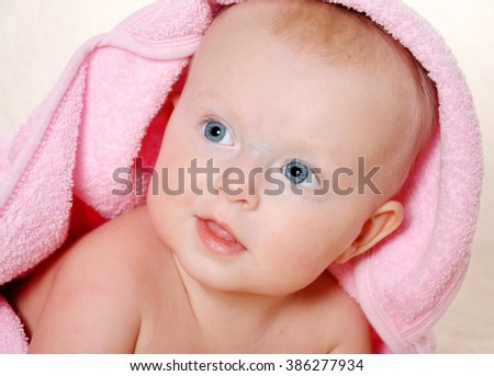 Adorable baby girl looking  under a pink towel - stock photo
