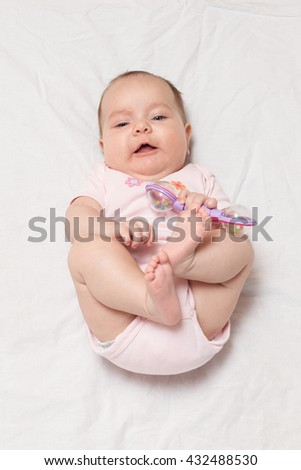 Adorable baby girl lying on her back trying to grab and hold her legs. Looking straight to the camera.