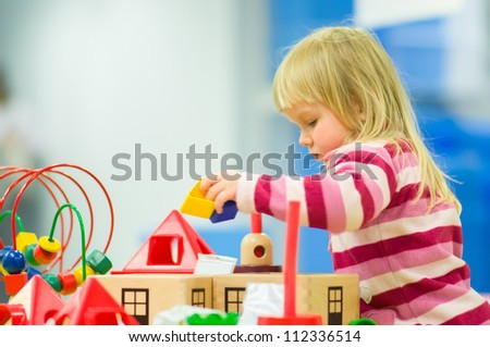 Adorable baby girl play with toys on table in mall - stock photo