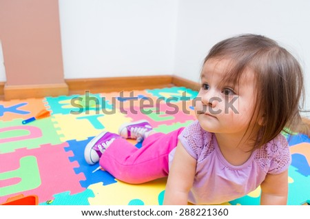 Adorable baby girl playing on floor in front of camera and looking to the side with curiousity - stock photo
