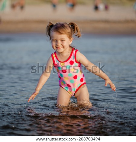 Adorable baby girl playing with a water in the sea - stock photo